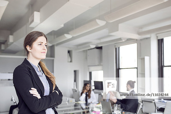 Confident businesswoman standing with colleagues discussing in background