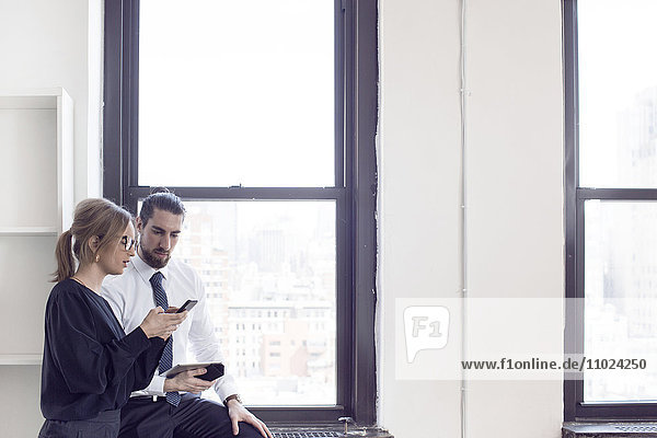 Businesswoman showing phone to male colleague by glass window