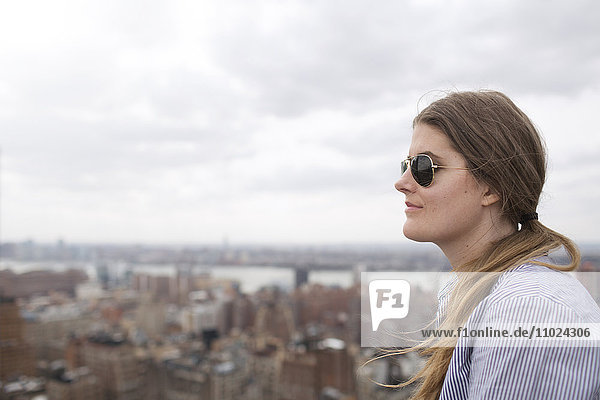 Close-up of thoughtful woman looking at city against sky