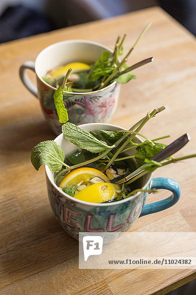 Sweden  Stockholm  Gamla Stan  Two cups with leaves and lemon slices Sweden, Stockholm, Gamla Stan, Two cups with leaves and lemon slices