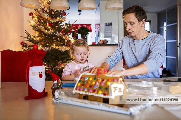 Father and daughter with gingerbread house at table during Christmas
