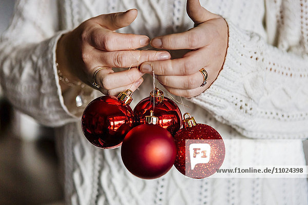 Midsection of woman holding red Christmas baubles
