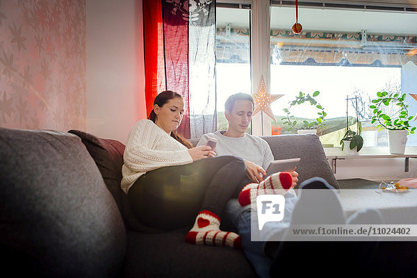 Couple using tablet and smart phone while relaxing on sofa at home