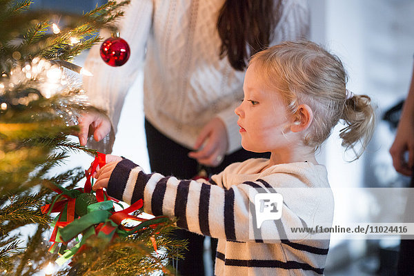 Mother helping daughter in decorating Christmas tree at home