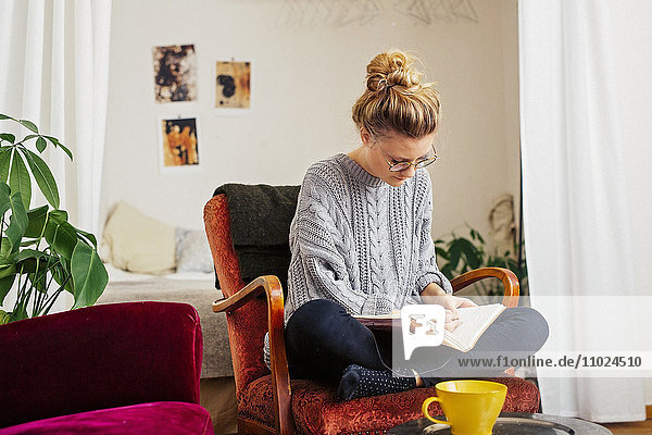 Woman writing on book while sitting on chair at home Woman writing on book while sitting on chair at home
