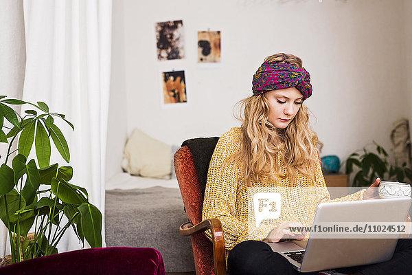 Woman wearing bandana using laptop while sitting at home Woman wearing bandana using laptop while sitting at home