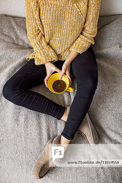 Low section of woman holding coffee cup while resting on bed Low section of woman holding coffee cup while resting on bed