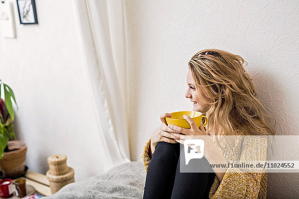 Smiling woman holding coffee cup while sitting on bed against wall
