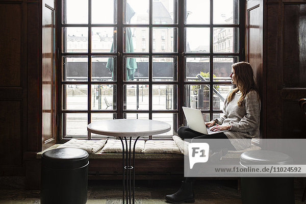 Young woman using laptop while looking through window at cafe