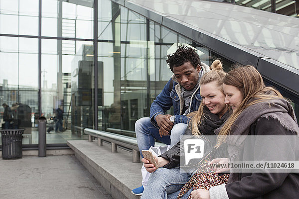 Friends looking at smart phone while sitting on retaining wall by glass building