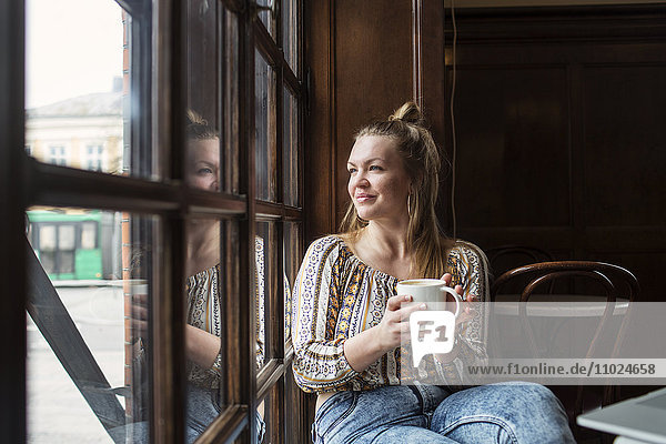 Thoughtful woman looking through window while sitting at cafe