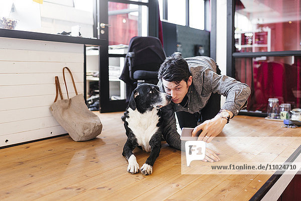 Businessman with dog taking selfie through smart phone at office