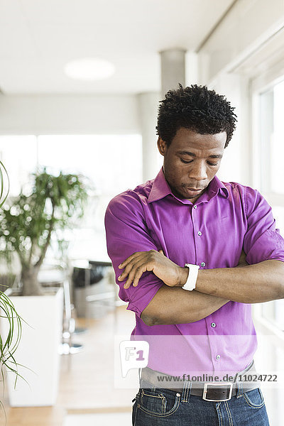 Young businessman looking at smart watch while standing in office