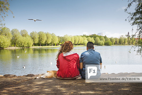 Rear view of man and woman sitting on lakeshore