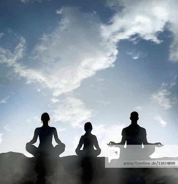 Silhouette einer meditierenden Familie gegen blauen Himmel im Lotussitz