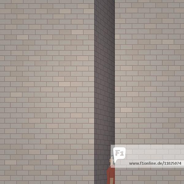 Frau gefangen zwischen zwei hohen Ziegelmauern