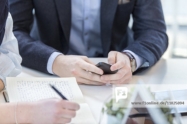 Midsection of businessman using phone while sitting with female colleague in meeting