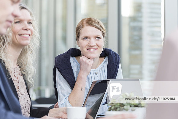 Happy businesswomen sitting in meeting at office