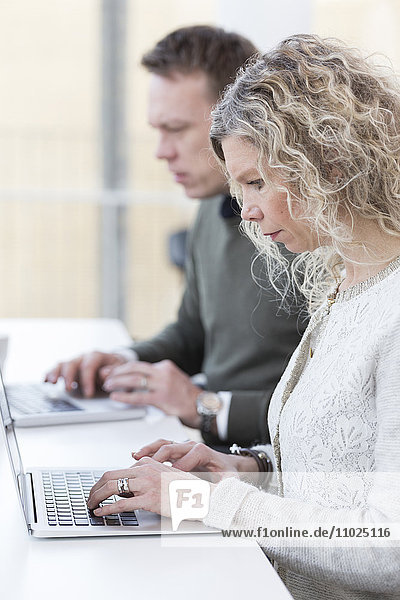 Businesswoman using laptop while sitting with male colleague in office