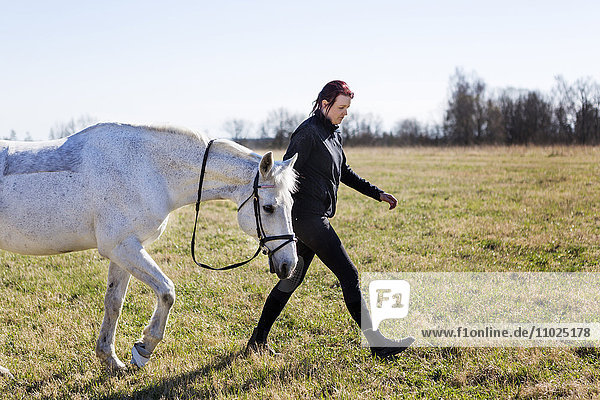 Side view of woman walking with horse on field