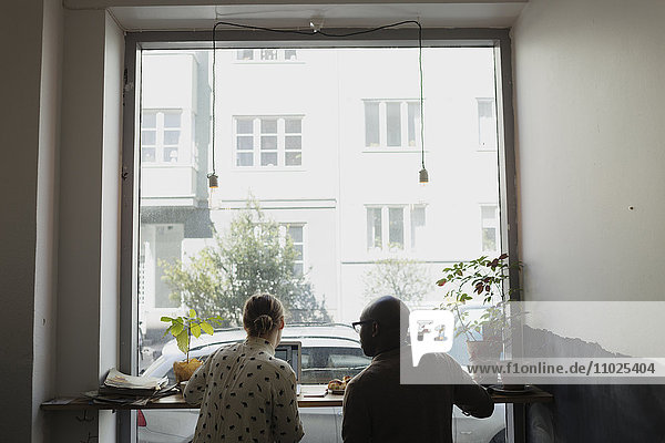 Rear view of business people working against window in cafe