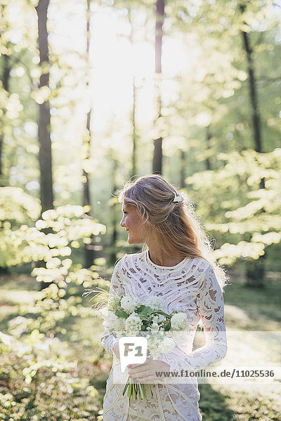 Beautiful bride holding bouquet in forest Beautiful bride holding bouquet in forest