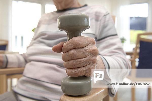 Krafttraining mit Handhantel im Seniorenheim