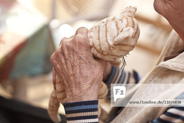 Seniorin mit Stofftier im Seniorenheim