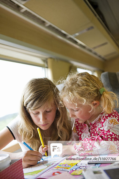 Girls sitting in train and drawing