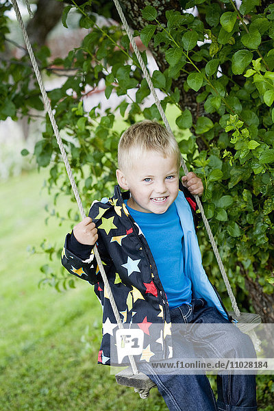 Boy sitting on swing
