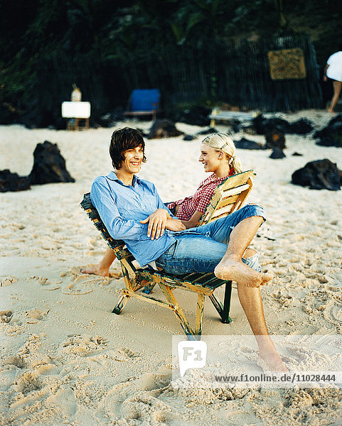 A man and a woman sitting in sun chairs on a beach.