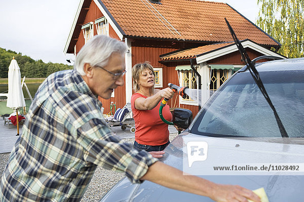 A man and a woman washing their car outside their house.
