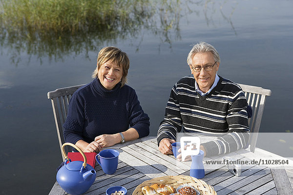 A smiling couple sitting on a patio by a lake.
