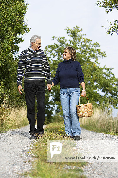 A couple holding hands on a walk.