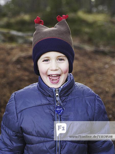 Boy (4-5) wearing knit hat laughing  portrait