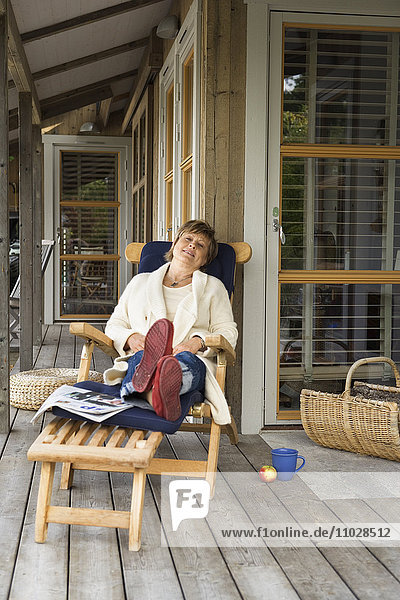 A woman resting in a sun chair on a porch.
