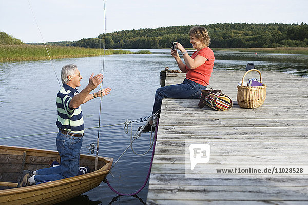 A woman photographing a man in a boat.