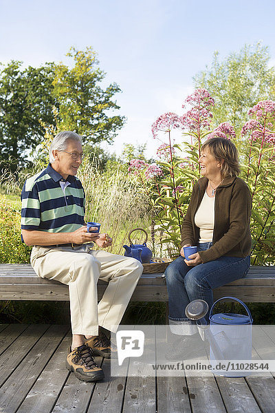A man and a woman drinking tea on a bench outdoors.