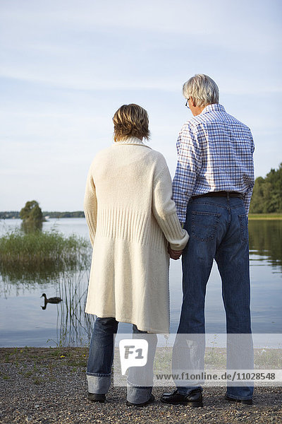 A man and a woman holding hands by a lake.
