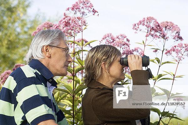 A woman looking in a pair of binoculars  a man standing behind.
