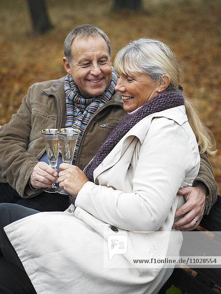 A couple toasting in champagne on a bench outdoors.