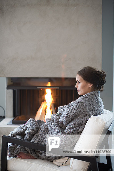 Young woman sitting in front of fireplace