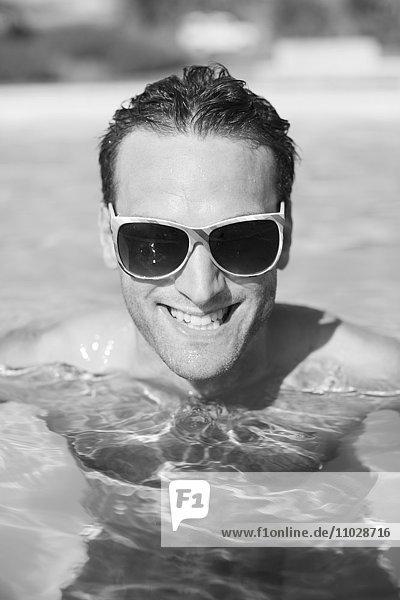 Mid adult man swimming in swimming pool