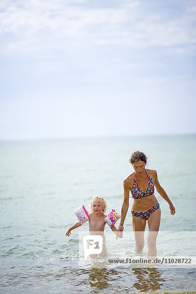 Mother and daughter walking in sea