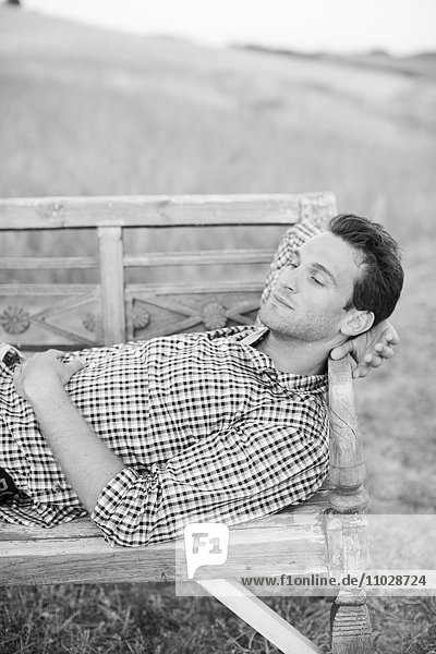 Mid adult man resting on bench