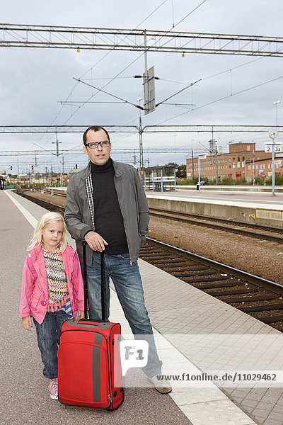 Father and daughter waiting for train
