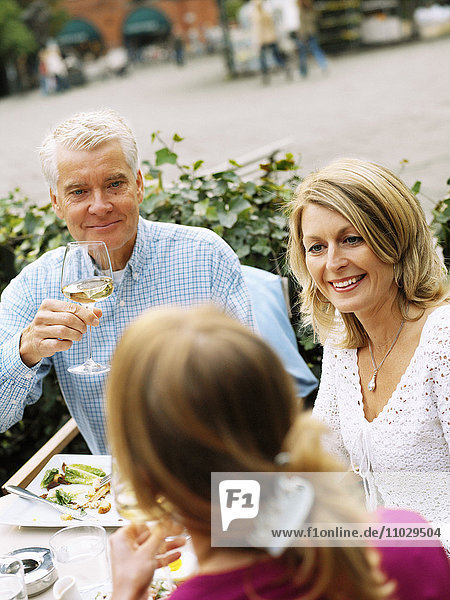 A man and two women having dinner outdoors.