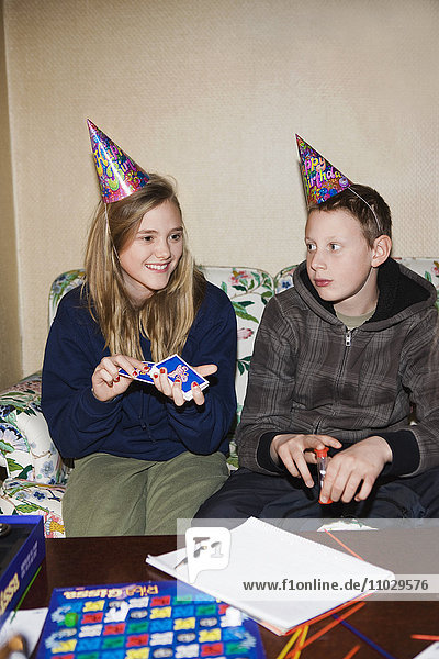 Teenage boy and girl wearing party hat  playing cards