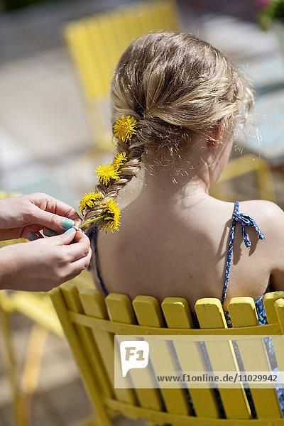 Girl braiding dandelion flowers into her friends hair
