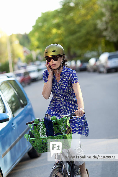 Woman cycling while talking via cell phone